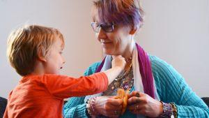 Vili Koskela tarkastelee äitinsä Annika Koskelan kaulakoruja