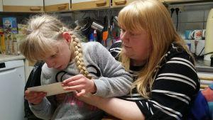 Tuija on alkanut kiinnostua omasta keskostaustaan ja tutkii vauvakuvia tarkkaan.