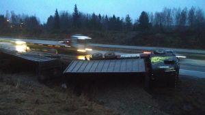 Täysperävaunullinen kuorma-auto kyljellään ojassa moottoritien varressa