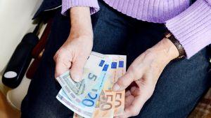 vanhemmalla naisella seteleitä kädessä