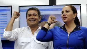 Hondurasin presidentti Juan Orlando Hernandez ja puoliso Ana Garcia de Hernandez tuulettavat hymyillen.