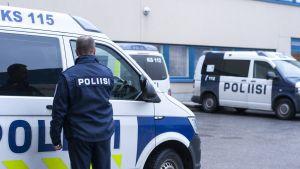 Poliisi menossa autoonsa ja taustalla lisää poliisiautoja