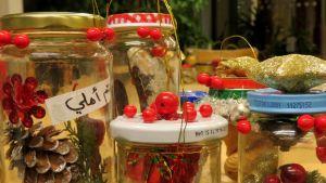 Lasipurkkeja, joissa on sisällä joulukoristeita ja metallilankakahva. Yhden purkin kyljessä on arabiankielistä tekstiä.