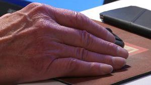 Miehen käsi pitää tietokoneen hiirtä.