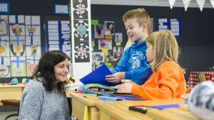 Lapset esittelevät töitään opettajalle.