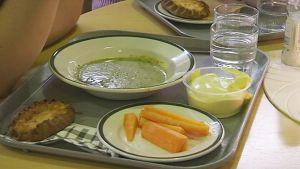 Pinaattikeittoa lautasella, karjalanpiirakka ja porkkanoita toisella.