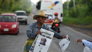 """Lehdenmyyjä pitelee käsissään lehteä toimittajamurhan jälkeen. Otsikossa lukee """"Me emme vaikene""""."""