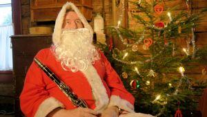 Joulupukki istuu kuusen vierestä...