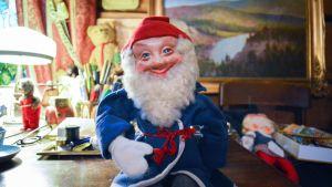 Vanha joulutonttunukke istuu työpöydän laidalla.