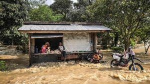Ihmisiä kaupan edustalla tulvien saartamana Kabacassa Mindanaon saarella 23. joulukuuta.