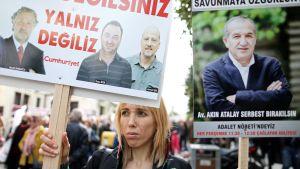 Nainen pitelee kylttiä jossa vastustetaan Turkin hallituksen tekemiä pidätyksiä.