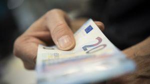Mies ojentaa kahdenkymmenen euron seteliä.