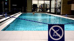 Nainen uimassa uima-altaassa.