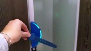 naisen käsi työntää elektronista ranneketta kohti pukukaapiin lukkoa