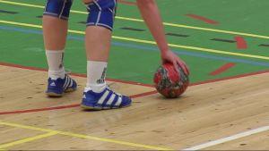 Bara benen syns när en spelare plockar upp en handboll