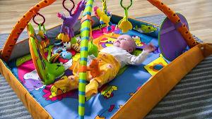 Vauva makaa leikkikaaren alla.