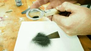 En hand som skakar ett svart färgpulver på en metallbit med hjälp av en liten sil.