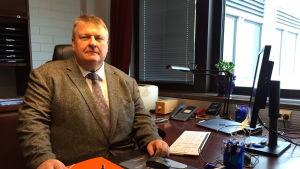 En person (Mats Perämaa) sitter vid ett skrivbord.