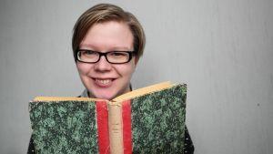 Hyllytontun höpinöitä -blogin Tiina katsoo kameraan kirjan takaa.
