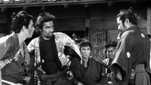 Kylän gangsterit uhittelevat samuraille (Toshiro Mifune) elokuvassa Yojimbo – onnensoturi