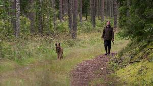 Olli Mustonen metsäkävelyllä koiransa kanssa.