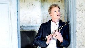 Klarinettisten Martin Fröst står i en dörröppning och håller i sin klarinettt