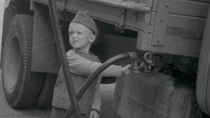 Poika tankkaa mustavalkokuvassa kuorma-autoa.