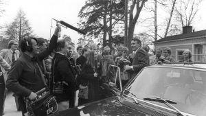 Mauno Koivisto stiger ut ur en bil och blir omringad av journalister.
