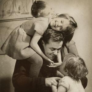 Isä keskellä tytär ja poika harteillaan ja pienin tytär sylissään olohuoneessa.