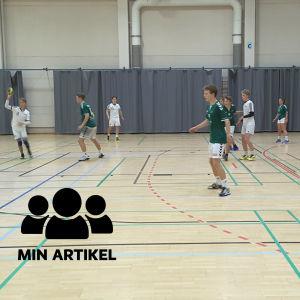 Tonåriga pojkar klädda i vita och gröna sportshorts och t-skjortor i en sporthall.