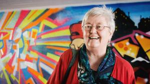 Haastateltava Raili Koskelainen kuvattuna Myyrmäenraitin alikulkutunnelissa, taustalla graffiteja.