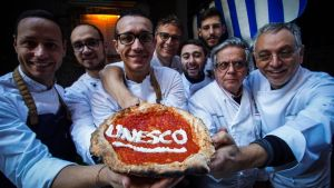 Åtta pizzabagare håller upp en napolitansk pizza där det står skrivet Unesco.