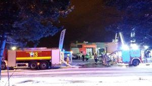 Brandkåren på plats en vinterkväll vid en brand i en bilverkstad.