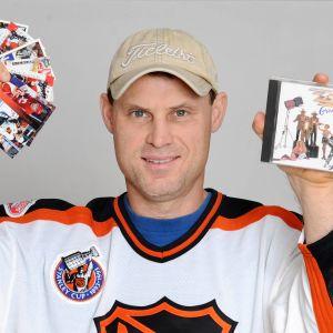 Zarley Zalapski visar upp hockeykort och en skiva.