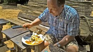 mies syö katukeittiössä Afrikassa, kissa kurkkii lautaselle