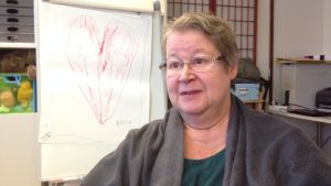 medelålders kvinna med glasögon sitter vid en tavla