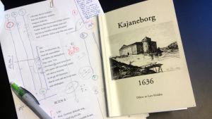 Manus och bok av Lars Huldèn på ett bord