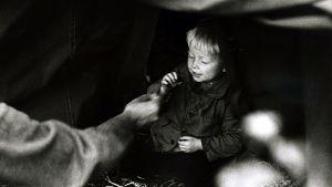 Ruotsiin saapuneiden evakoiden odotusta teltassa. Poikalapsi syö karamellia. (1942)