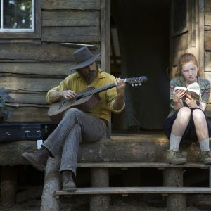 Far spelar gitarr och dotter läser på trappan till ett enkelt hus.