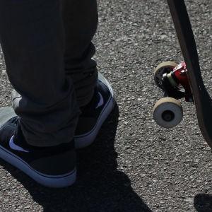 En skateboardåkares bräda och fötter.