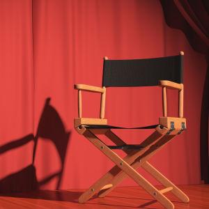 Regissörsstol framför draperi.