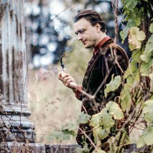 Viktor Granö som en av sina karaktärer med en pipa.