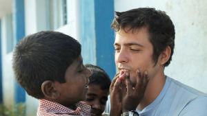 Ett indiskt barnhemsbarn trycker ihop Rockys underläpp.