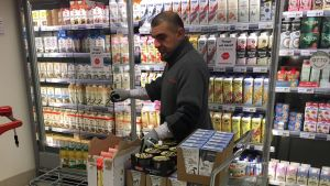 Butiksanställd plockar upp meijerivaror i en livsmedelsaffär.