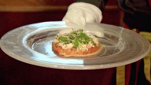 Tarjoilija tuo pöytään nouvelle cuisine -tyylistä annosta sarjassa Ruoka-aikoja