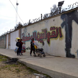 Irakiska pojkar i Mosul promenerar längs en vägg där Islamiska staten skrivit slagord