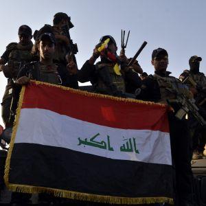 Irakiska elitsoldater firar fritagningen av Mosul och håller upp den irakiska flaggan på ett lastbilsflak.