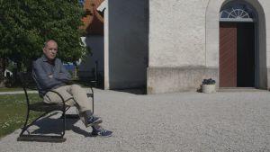 Jörn Donner sitter på en bänk utanför kyrkan på Fårö.