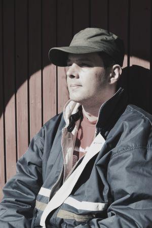 En man sitter i solsken vid röd trävägg.