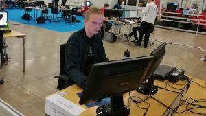 Ung svartklädd man sitter framför två datorskärmar i en stor sal där det också finns andra människor.